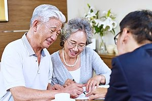 a retirement plans consultant assisting a retired couple as they sign a document for their 401k retirement plans