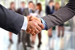 a handshake between a business owner and the owner of a financial consultants firm after discussing retirement plans for small businesses