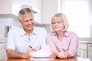 an elderly couple who are reading over their retirement plans that they recently signed up for