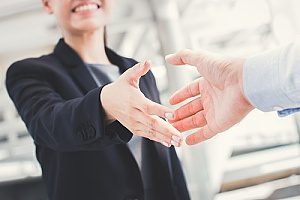 financial consultants shaking hands with an individual who is seeking retirement plans