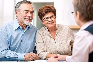 financial consultants speaking with an elderly couple about retirement plans