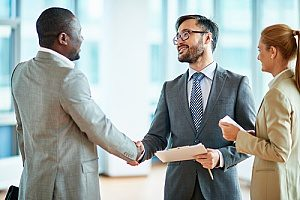 the owner of a financial consulting firm shaking hands with a small business owner in Fairfax, VA as they meet to talk about retirement plans for his employees